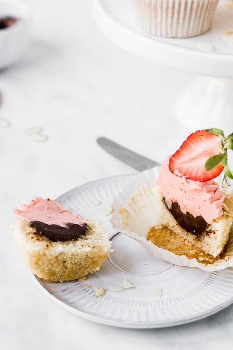 Strawberry cupcake cut in to showing the chocolate ganache by Emma Duckworth Bakes
