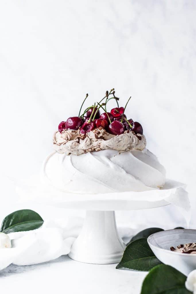 Meringue on a cake plate topped with chocolate cream and cherries