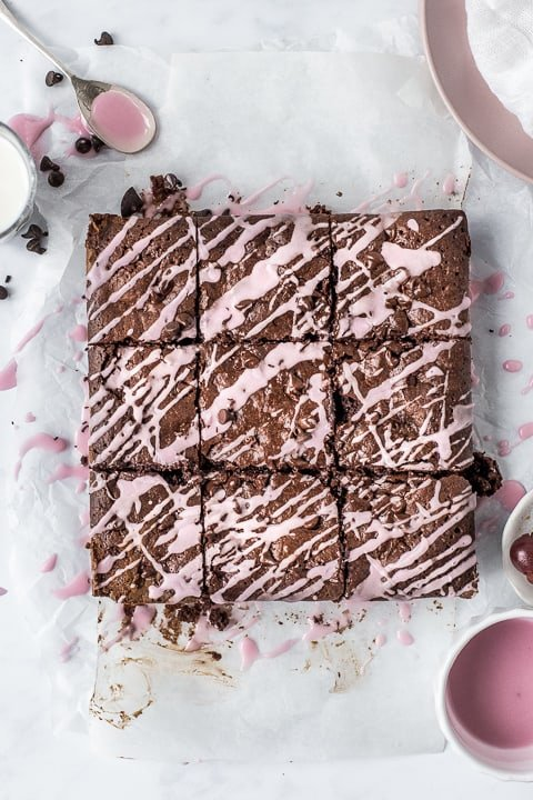 Chocolate cherry brownies cut into squares on a board