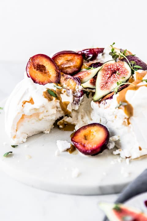 Crisp meringue with a fluffy interior, topped with whipped cream, roasted plums, fresh figs and toffee sauce by Emma Duckworth Bakes