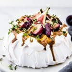 Billowy meringue topped with cream, roasted plums and fresh figs