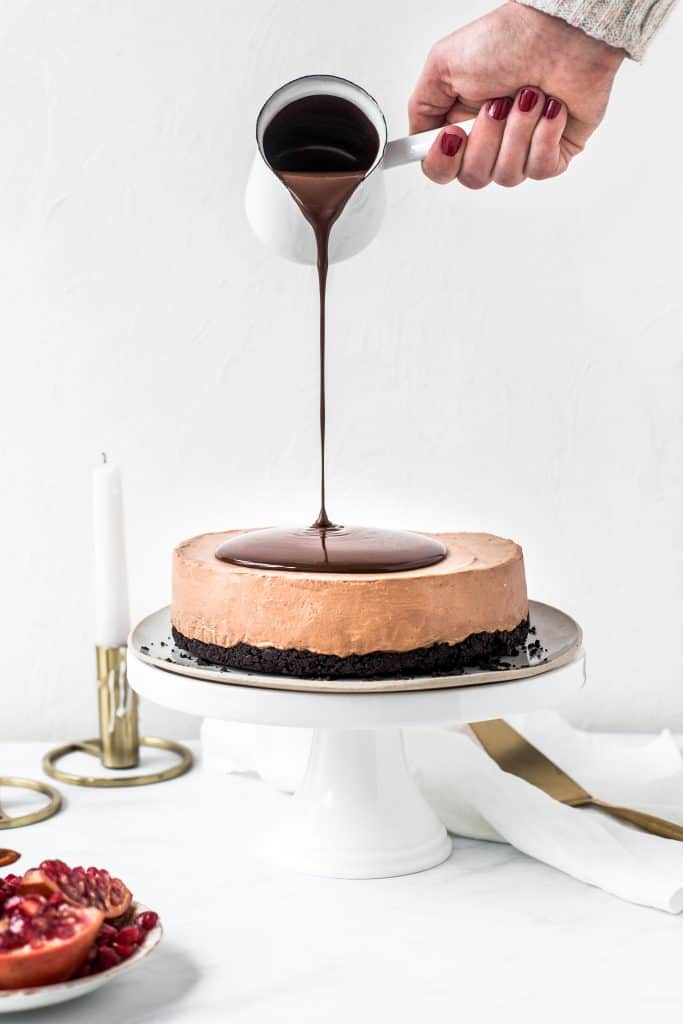 Triple Chocolate No-Bake Cheesecake, oreo crust with chocolate mascarpone cream cheese filling and a layer of chocolate ganache being poured on top.