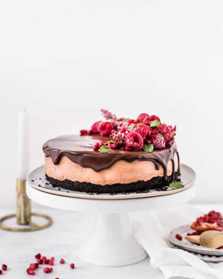 Triple Chocolate No-Bake Cheesecake, oreo crust with chocolate mascarpone cream cheese filling and a layer of chocolate ganache on top. Decorated with raspberries and pomegranate seeds.