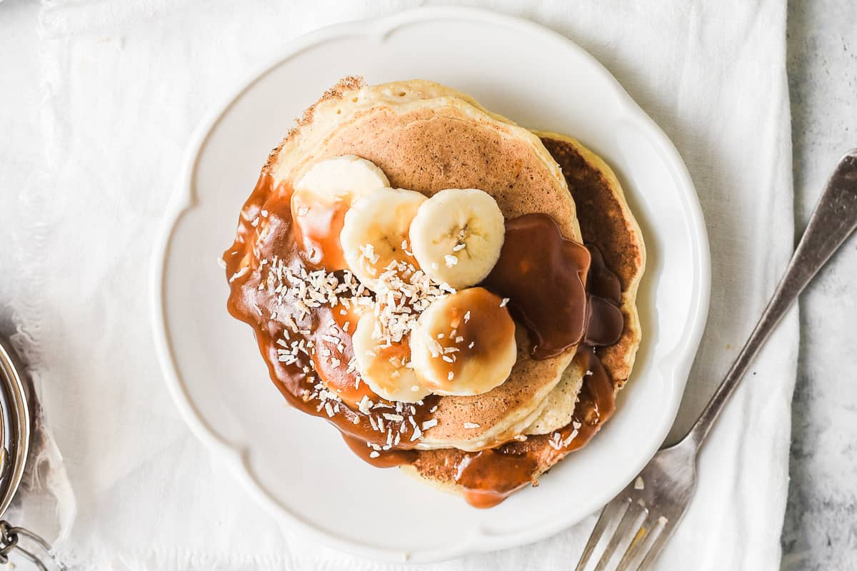 Scalloped plate serving ricotta pancakes with sliced fresh bananas and caramel sauce
