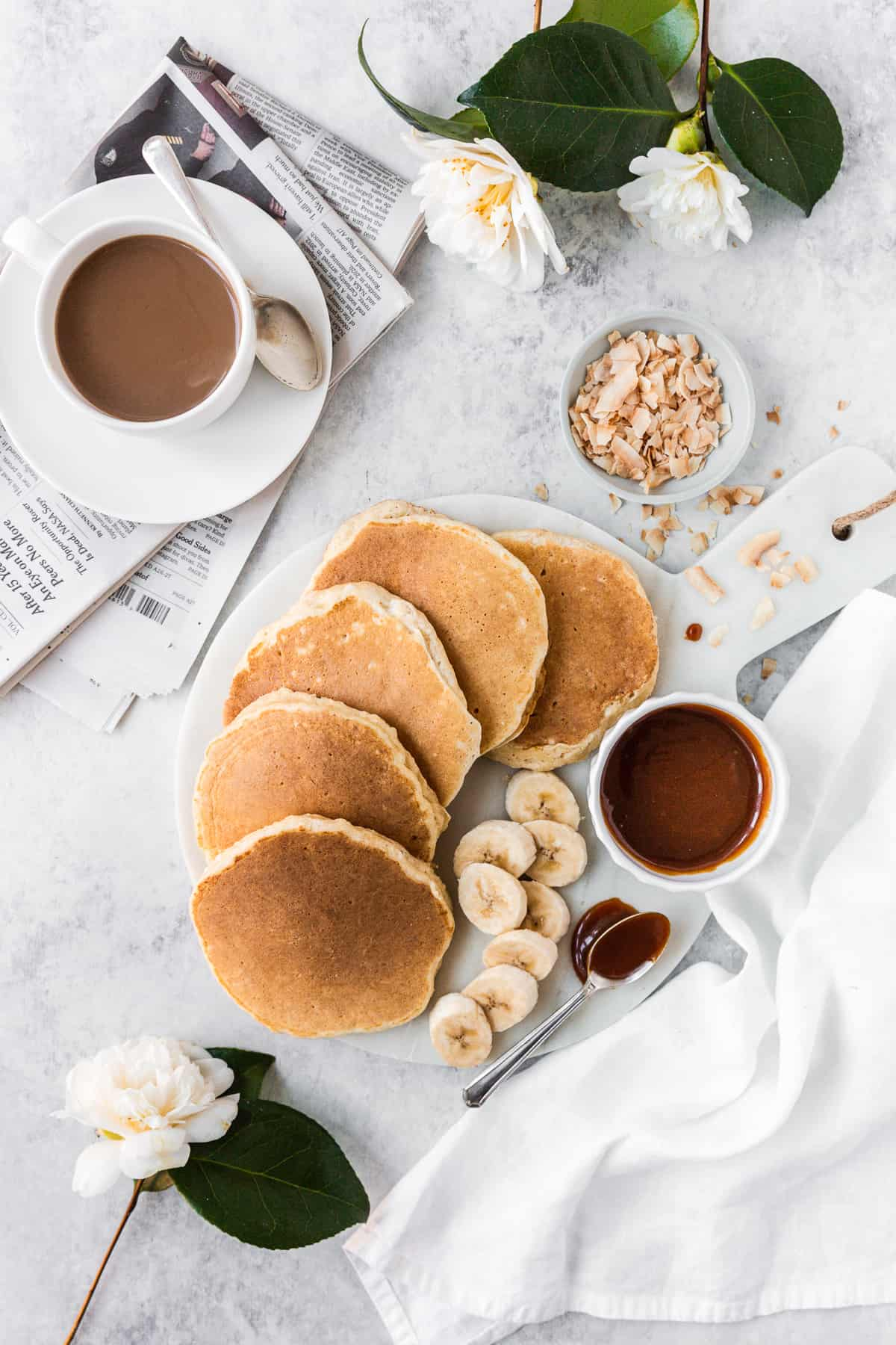 Breakfast scene with serving platter topped with ricotta pancakes, sliced banana and carmakers sauce.