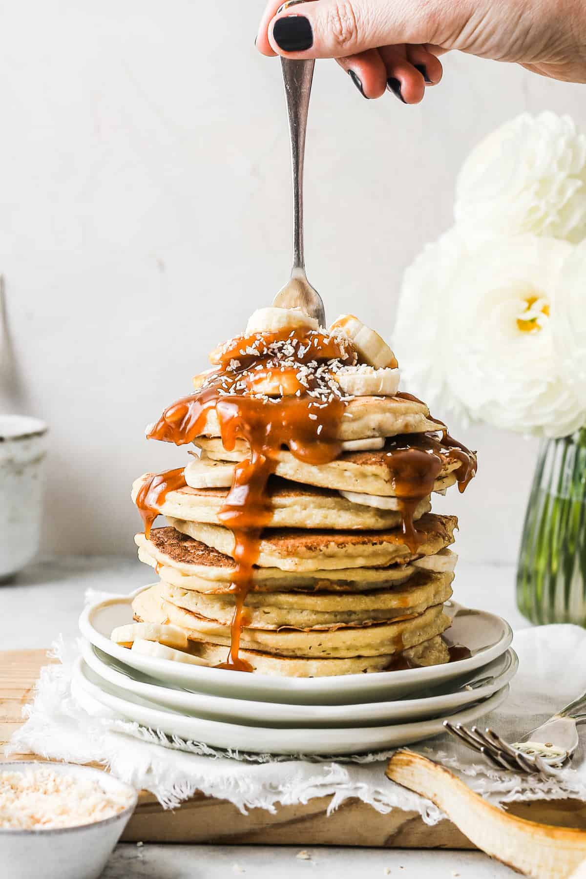 Stack of fluffy ricotta pancakes drizzled in caramel sauce and served with sliced bananas