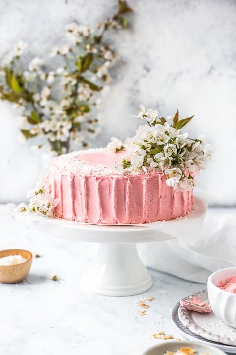 Pink cake on cake stand decorated in flowers