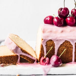 Pound cake covered in pink glaze and decorated with fresh cherries
