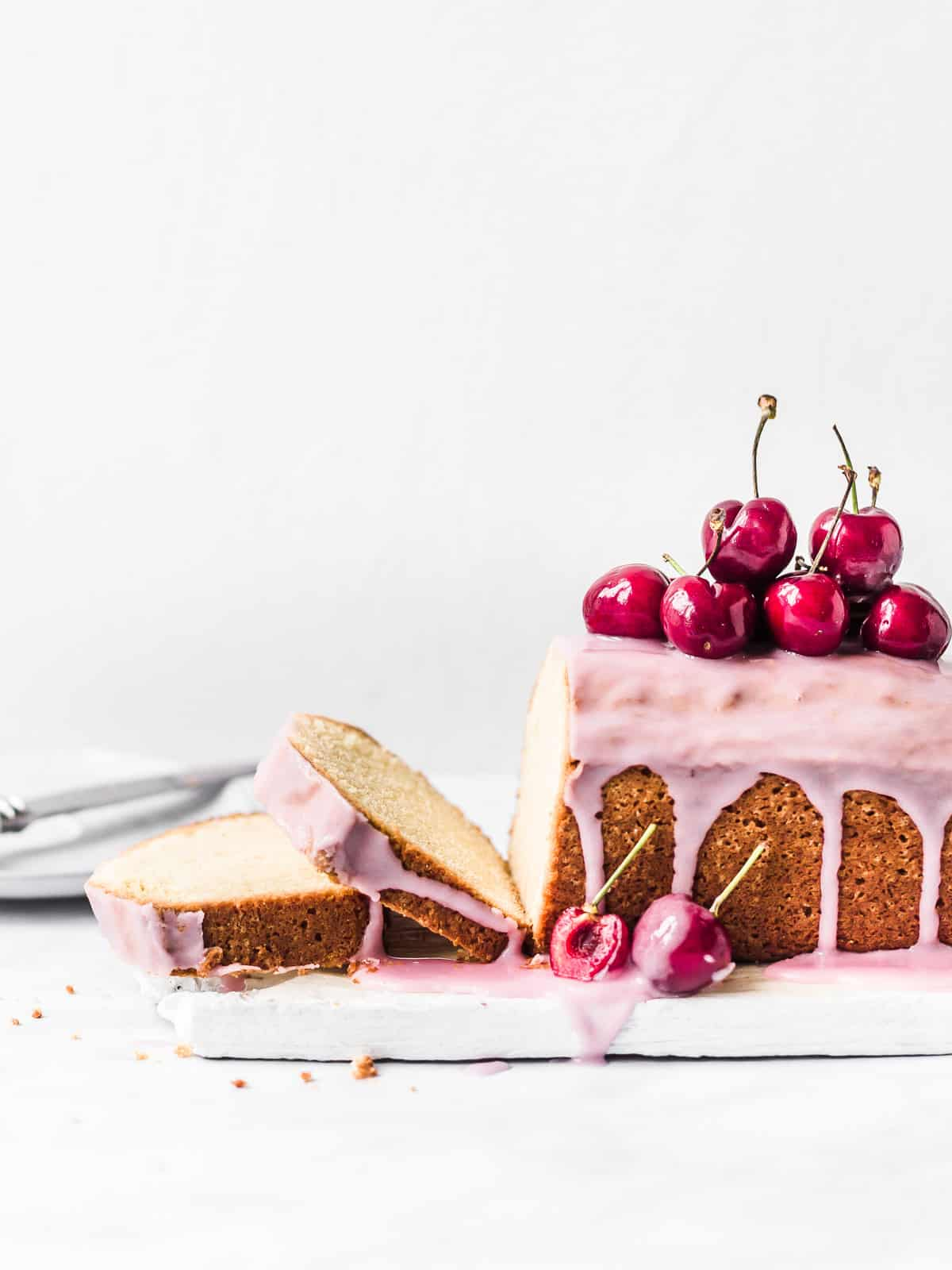 Orange Blossom Cake decorated with pink icing and fresh cherries