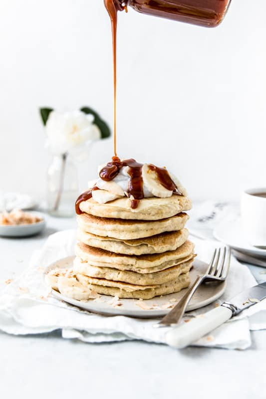 Stack of pancakes with caramel sauce being drizzled
