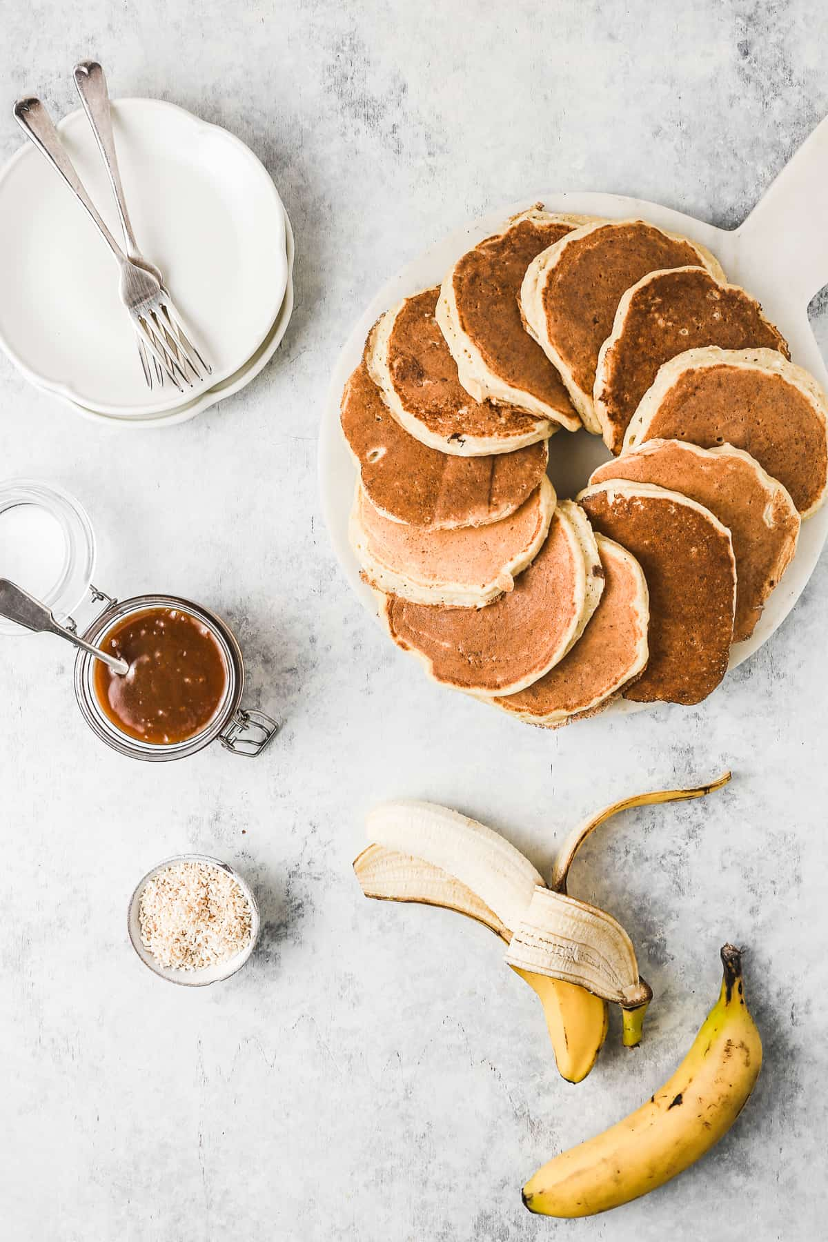 Serving platter of fluffy pancakes with sliced bananas and caramel sauce.