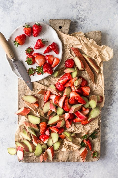 Rhubarb and strawberries cut on a chopping board