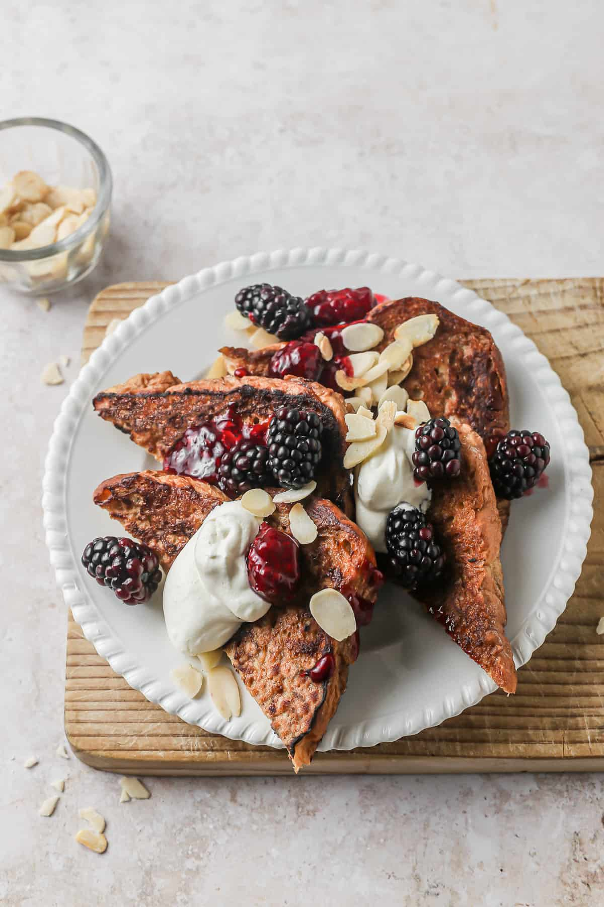 Earl Grey French Toast slices on a plate served with cream and blackberries