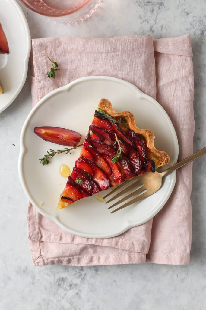 Plum Frangipane Tart Sliced on a white scalloped plate with pink napkin