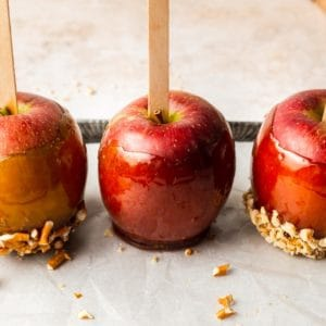 Three apples dipped in toffee on a tray
