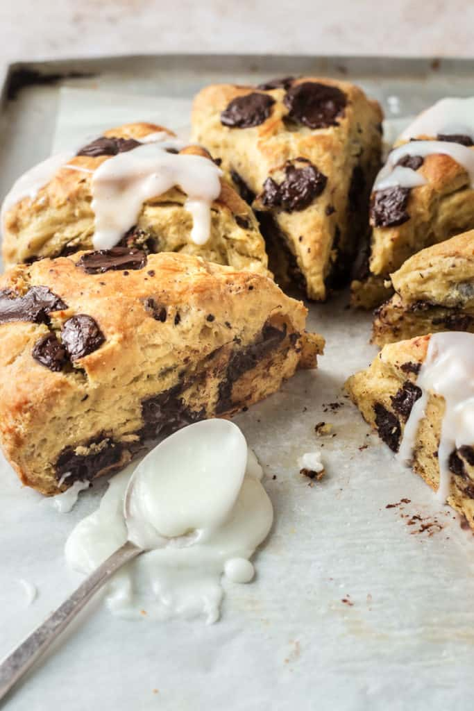 Glazed Chocolate Scone Recipe - close up of wedges with glaze spilling off spoon