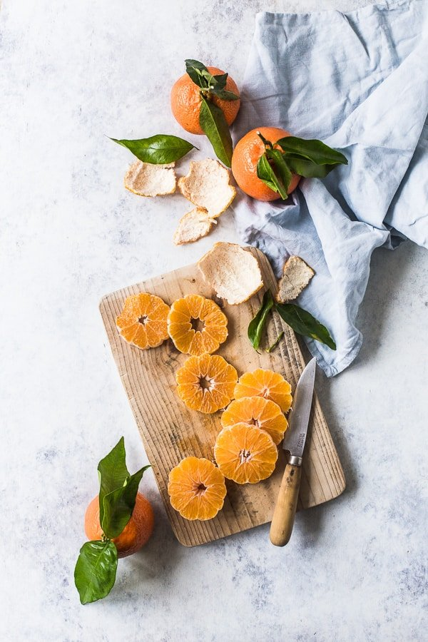 Clementines sliced on a wooden board