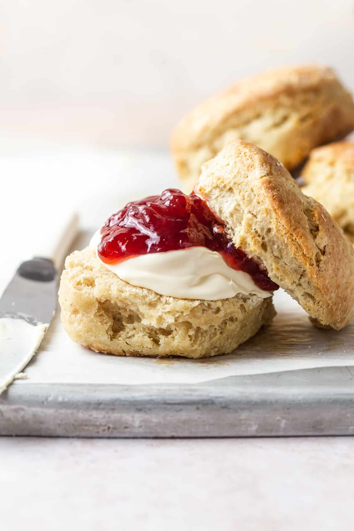 Foolproof scone recipe - scone on a plate served with cream and jam
