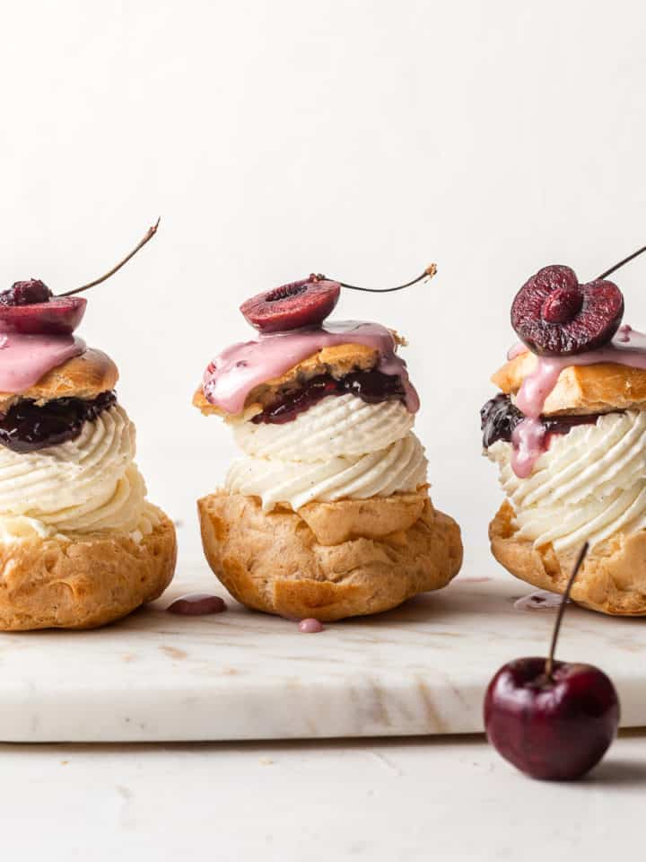 Three cherry cream puffs sat next to each other. Each one is topped with half a cherry