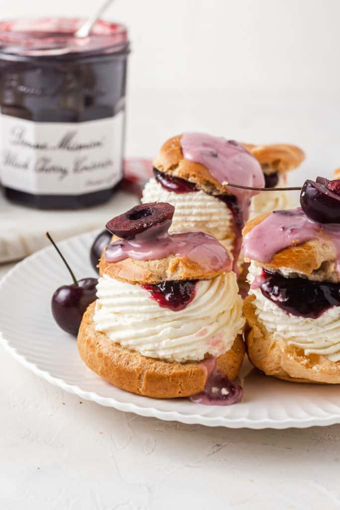 Multiple cherry cream puffs sat on a scalloped white plate with a jar of jam in the background.