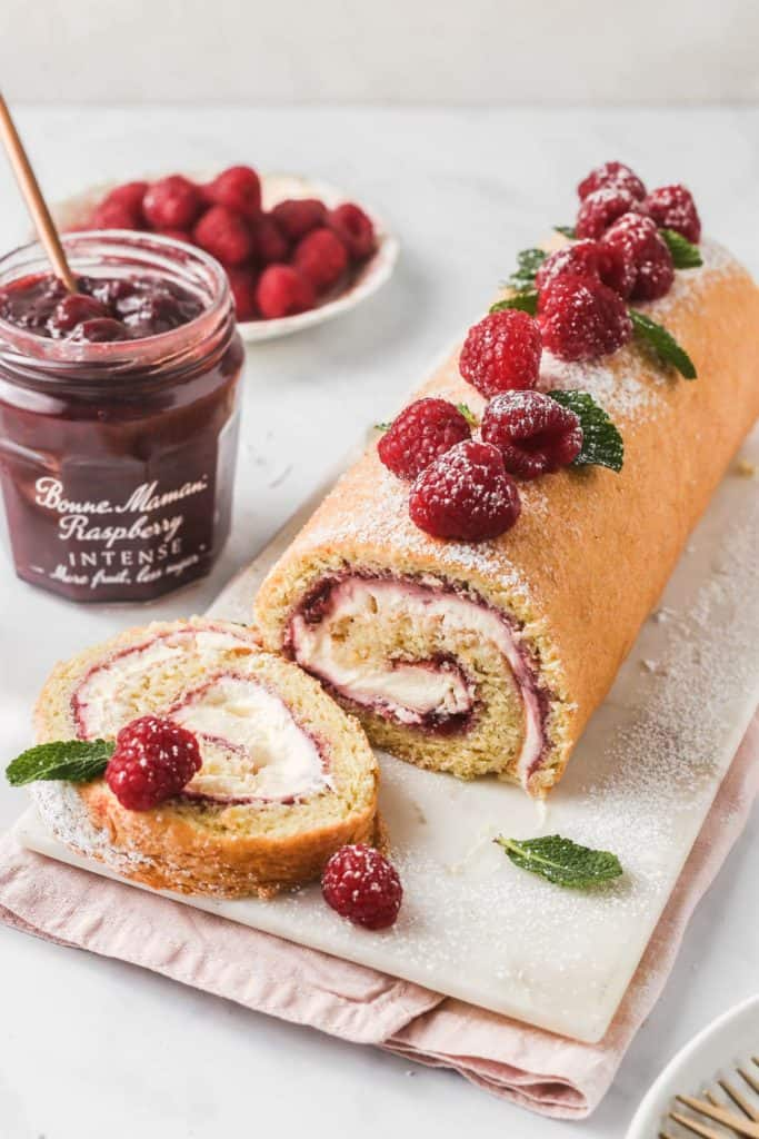 Fruit Swiss Roll with with slice on marble platter