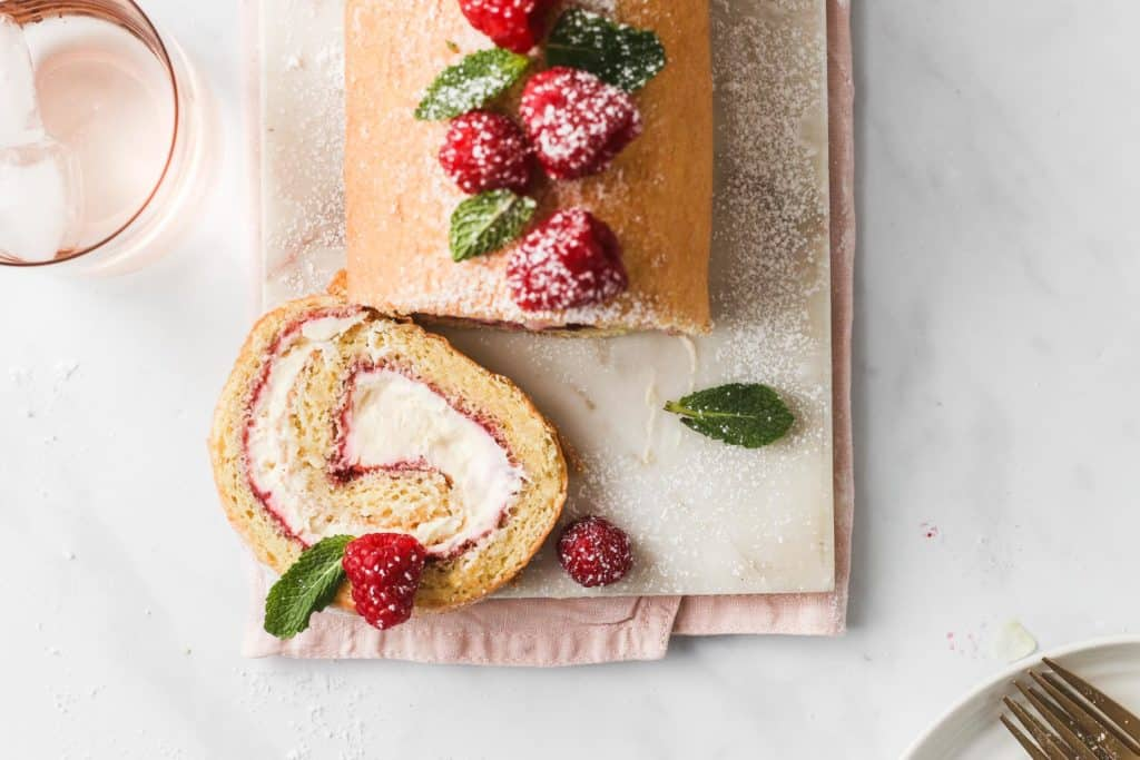 Top down view of Raspberry Swiss Roll decorated in fresh raspberries and mint leaves