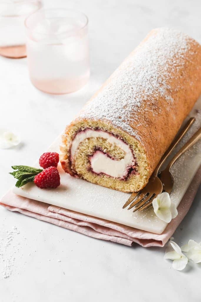 Raspberry Swiss Roll dusted in icing sugar on a marble platter