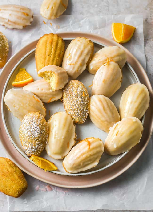 Soft buttery sponge lightly fragranced with orange and dipped into an orange glaze on a pink round dish. Orange Madeleines