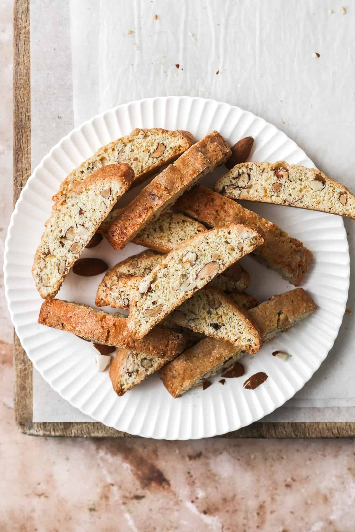 Classic almond biscotti piled on a scalloped plate