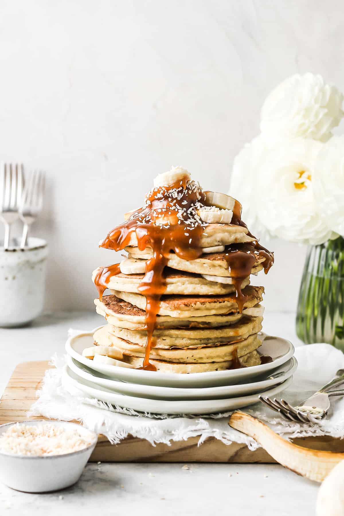 Stack of fluffy pancakes, topped with freshly sliced bananas and drizzled in caramel sauce