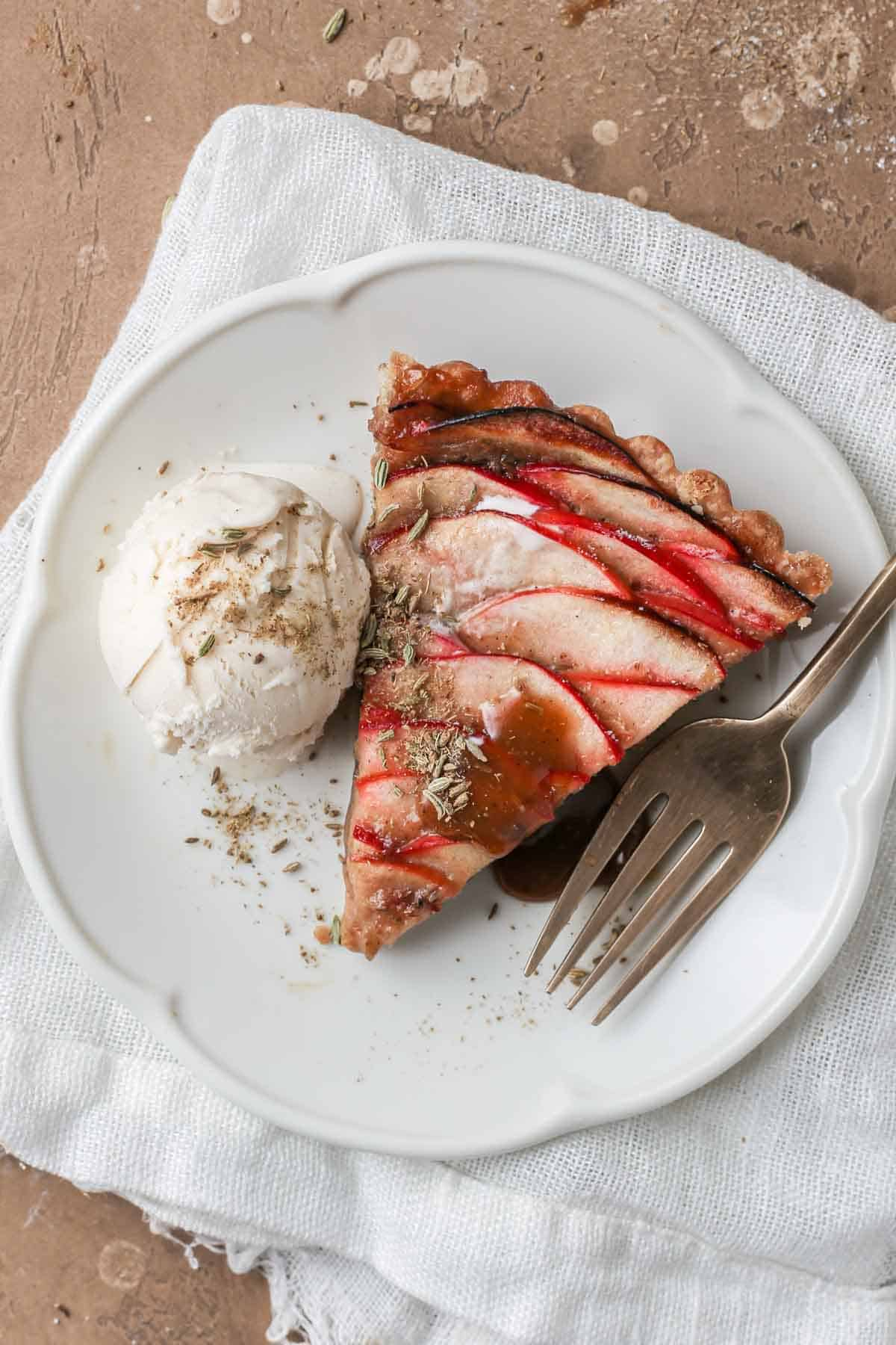 Slice of apple caramel tart, drizzled with fennel caramel and served with a scoop of ice-cream.